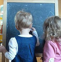 Two children writing on blackboard shot from behind