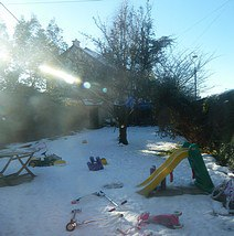 Snow covered garden scattered with children's toys