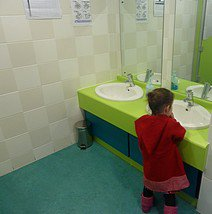 Smal child standing at sink washing hands